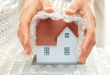 Woman hands covering a model house with bubble wrap- house protection or insurance concept