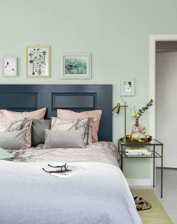 En grön väggfärg i sovrummet bidrar till en lugn och skön känsla. Väggen och tavelramarna är målade i kulören Saltsten 799, golvet ikulören Klippa 508 och sänggaveln i kulören Midnatt 772. Foto: Beckers