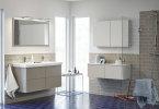 Låt förvaringslösningen ge en trevlig rumskänsla. Här med toner i lugnt sandbeige kombinerat med ett lite överraskande blått golv. Kaklet stannar på halva väggen för att skapa variation och dynamik.Foto: Vedum Kök och Bad.