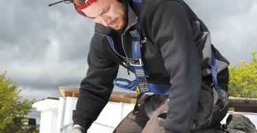 Byggnadsplåtslagare som falsar ett plåttak. Med rätt underhåll skyddar taket byggnaden i uppåt 100 år. Foto: Cecilia Nordstrand.